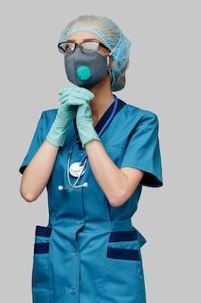 Врач медсестра женщина носить защитную маску и латексные перчатки - молиться над надеждой жест