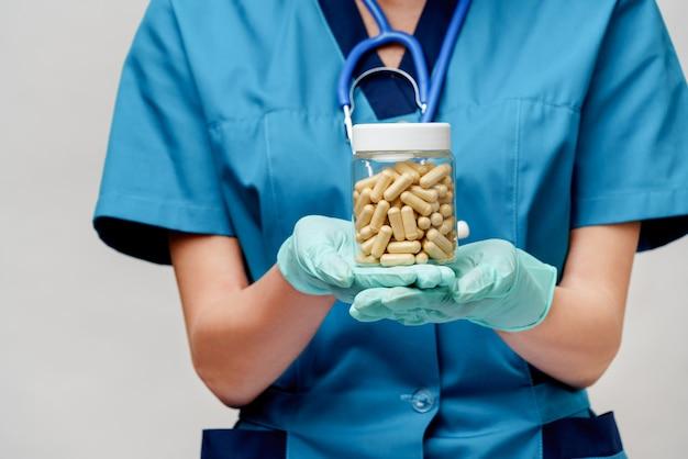 保護マスクとゴムまたはラテックスの手袋を着用して医師看護師女性-薬を保持
