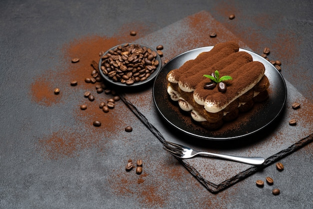 Классический десерт тирамису на керамической плите на бетонной поверхности