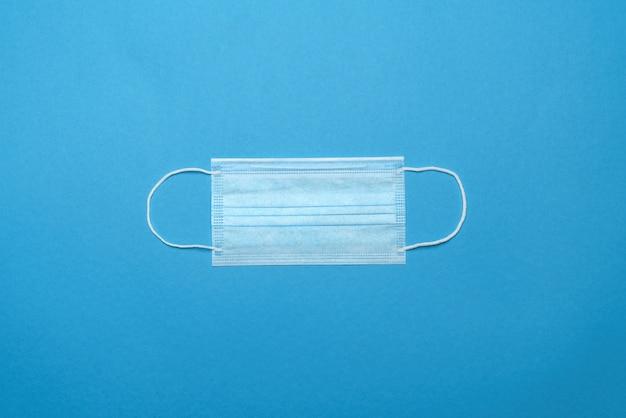 Одноразовая синяя медицинская маска на синем фоне