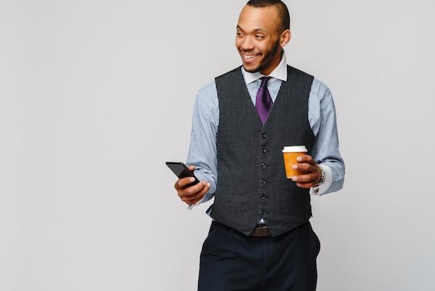 電話とコーヒーを保持している若いアフリカ系アメリカ人のビジネスマンは、ライトグレーを越えます。
