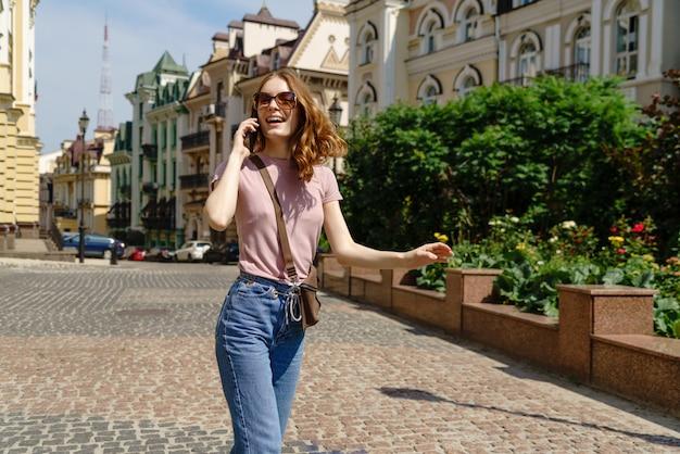 Красивая молодая женщина турист в центре города, разговаривает по телефону.