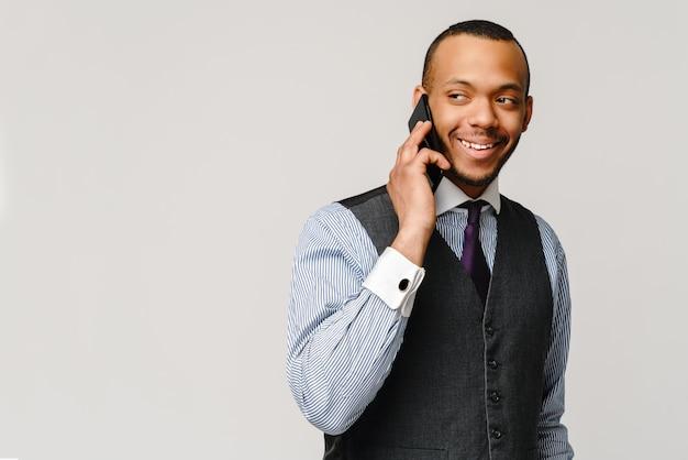 モバイル携帯電話で話しているプロのアフリカ系アメリカ人ビジネスの男性