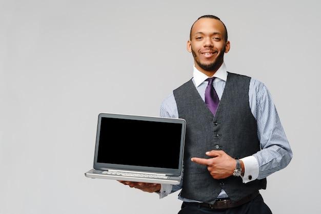 ラップトップコンピューターを保持しているプロのアフリカ系アメリカ人ビジネス男