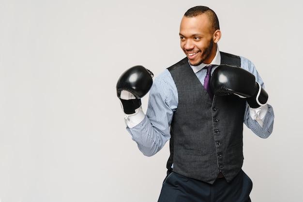 怒っている動揺の若い男性会社員、会社員、ボクシンググローブで空気中の拳、口を開けて叫び、否定的な感情の表情の感情。