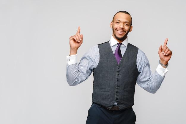 灰色の壁を越えて指で現れるアフリカ系アメリカ人の実業家。