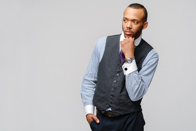 灰色の壁の上の若いアフリカ系アメリカ人の実業家。