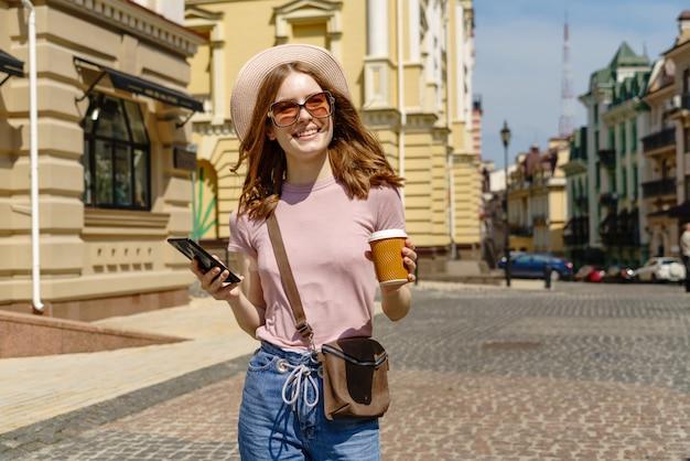 Красивая молодая женщина турист с вынос кофе в центре города, разговаривает по телефону.