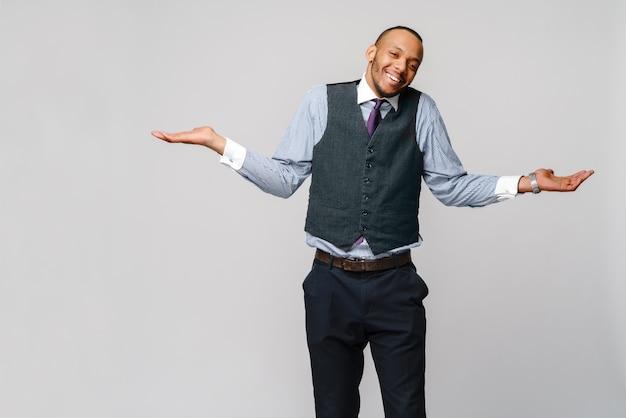 疑わしいコンセプト-ネクタイを身に着けている若いアフリカ系アメリカ人実業家と明るい灰色の壁の上に腕と手を上げた無知と混乱した表情。