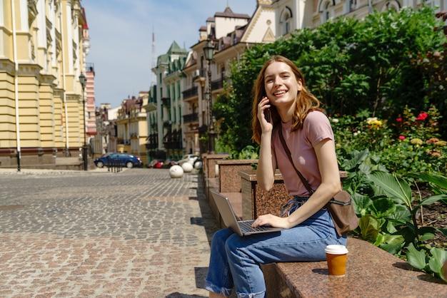 ラップトップを使用して市内中心部でテイクアウトのコーヒーを飲みながら美しい若い女性観光客。
