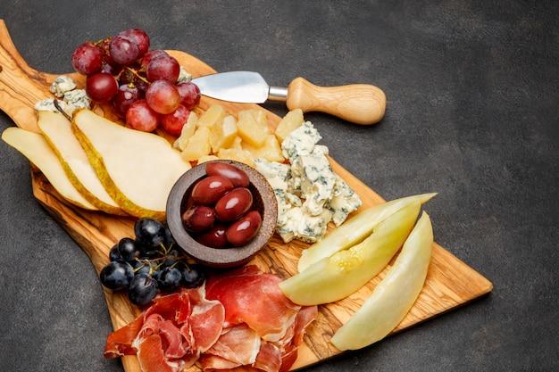 Мясная тарелка закуска закуска - ветчина прошутто, сыр с плесенью, дыня, виноград, оливки