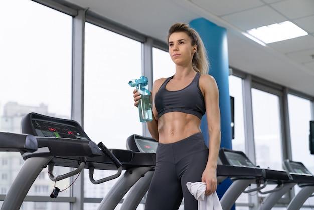 Женщина спортзала разрабатывая тренажеры питьевой воды готовя