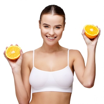Портрет привлекательной улыбающейся женщины, держащей апельсин на белом фоне