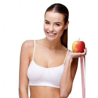 Портрет привлекательной улыбающейся женщины, держащей яблоко на белом фоне