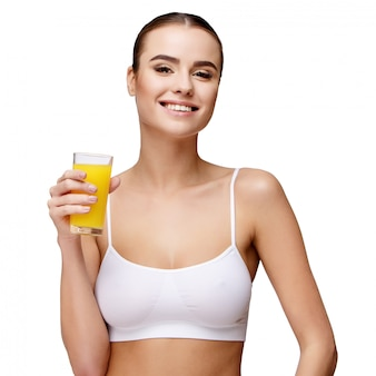Привлекательная улыбающаяся женщина, держащая стакан апельсинового сока на белом