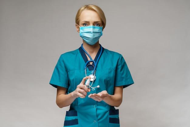 消毒スプレーまたはジェルのボトルを保持している保護マスクを身に着けている医師看護師