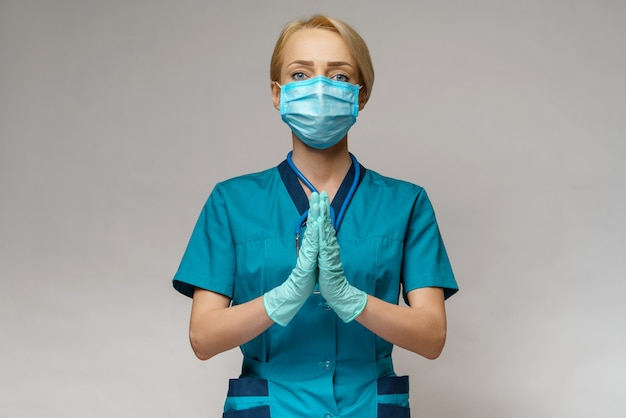 Женщина-врач в защитной маске и латексных перчатках молилась над надеждой на жест