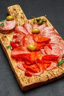 Холодная мясная тарелка с колбасой салями и чоризо на пробковой доске