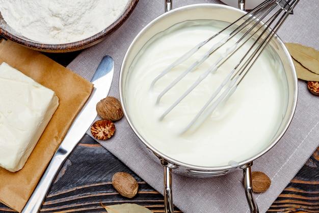 Соус бешамель в сковороде и ингредиенты