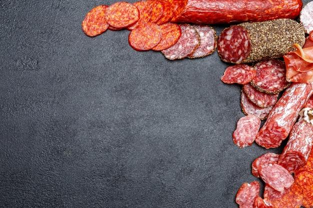 Различные виды сушеных органических колбасы салями на бетонном фоне