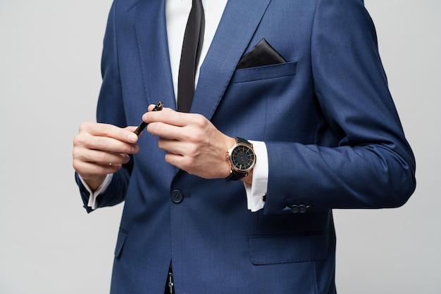 Фото конца-вверх ручки удерживания костюма молодого бизнесмена нося