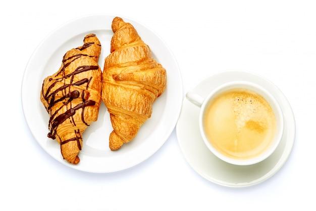 Два свежих круассана и кофе на белом фоне