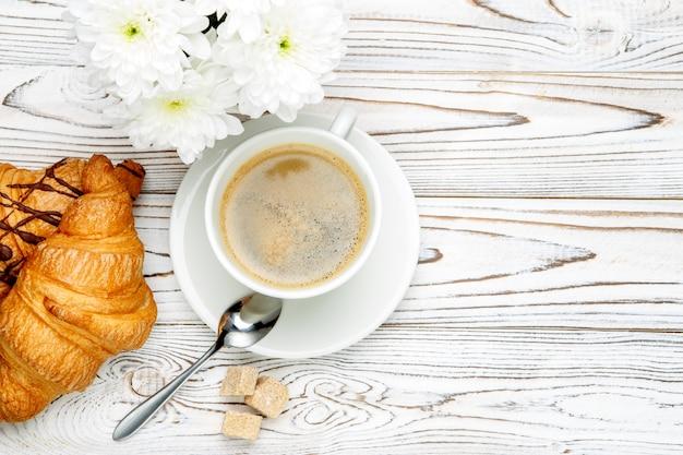 Два свежих круассана и кофе, цветы на деревянном фоне