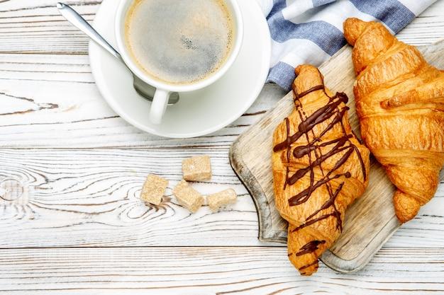 Два свежих круассана и кофе на деревянном фоне