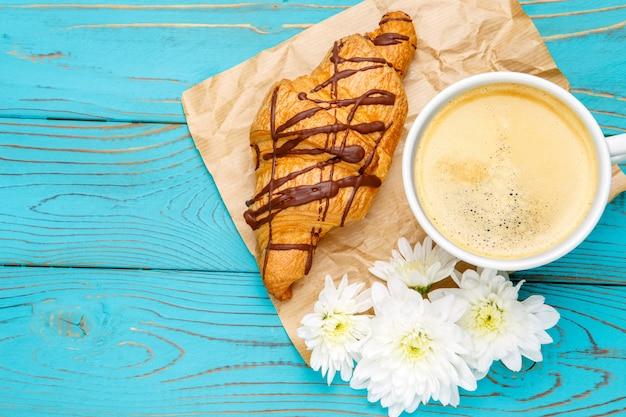 Свежий круассан и кофе на деревянном фоне