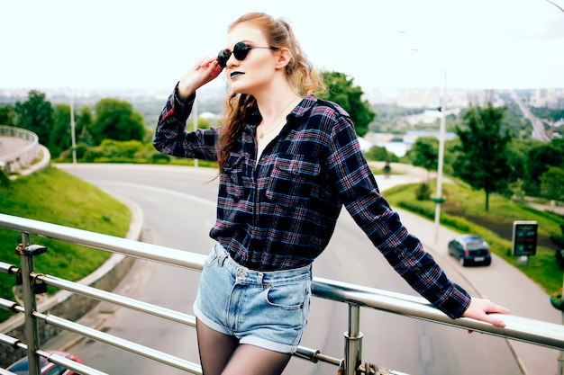 Летний портрет красивой худой хипстерской девушки в клетчатой рубашке и джинсовых шортах в стильных солнечных очках и синей помаде