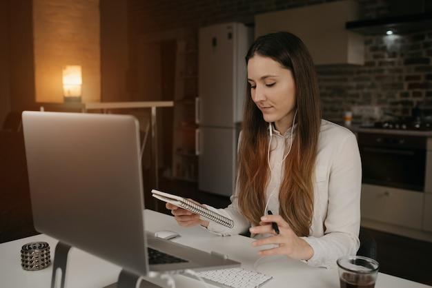 リモート作業。彼女のラップトップでリモートで作業するヘッドフォンを持つ白人女性。居心地の良い自宅でのオンラインビジネスブリーフィング中にメモを探している白いシャツの女の子。