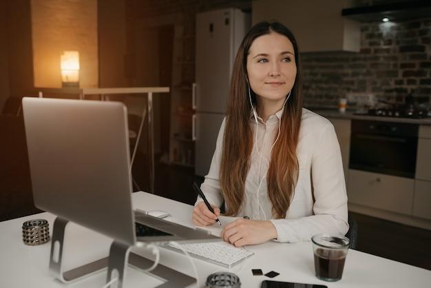 リモート作業。彼女のラップトップでリモートで作業するヘッドフォンを持つ白人女性。彼女の居心地の良い自宅の職場でのオンラインビジネスブリーフィング中にメモをして笑顔で幸せなブルネットの少女。