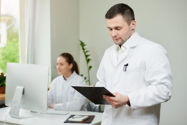 白いコートの剛毛を持つ外科医が黒いクリップボードを保持