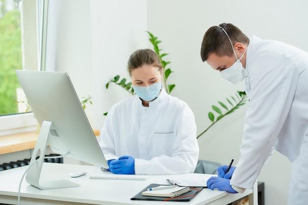 フェイスマスクの外科医と放射線科医が患者の分析について話し合う