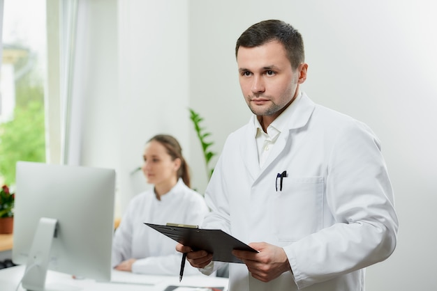 剛毛を持つ深刻な外科医が黒いクリップボードを保持