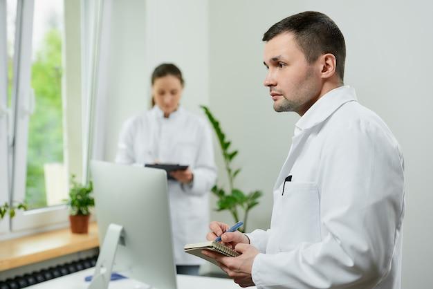 白人医師が女性セラピストの近くにペンでメモを取る