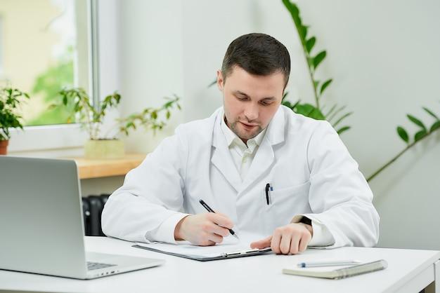 Кавказский врач в белом халате заполняя карточку пациента с диагнозом