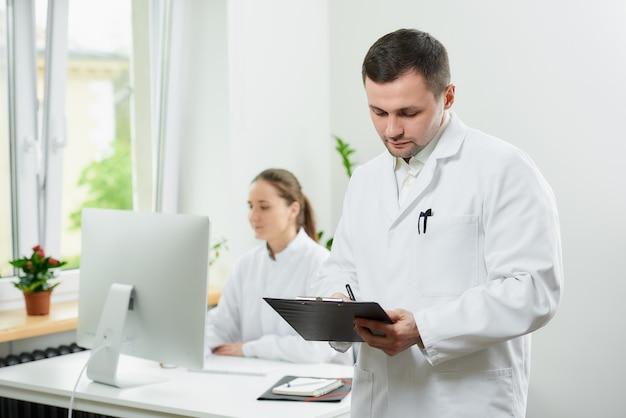 Серьезный хирург с щетиной в белом халате заполняет карточку пациента