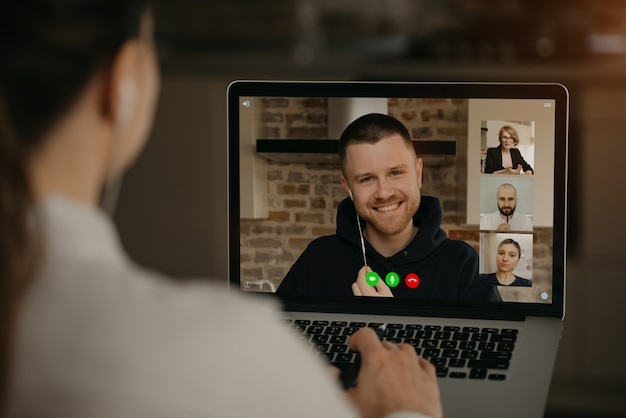 Вид сзади женщина разговаривает с деловым партнером и коллегами в видео звонок на ноутбуке. человек разговаривает с коллегами по конференции веб-камера. многонациональная бизнес-команда с онлайн-встречей