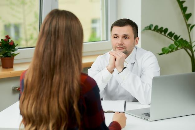 机に座って、患者の話を聞いて白衣の白人医師
