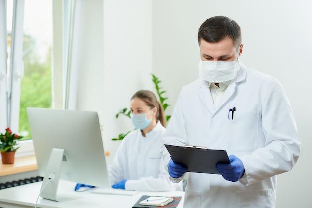 Хирург с щетиной носит респиратор и заполняет карточку пациента
