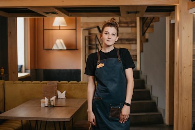 Молодая официантка позирует в ресторане