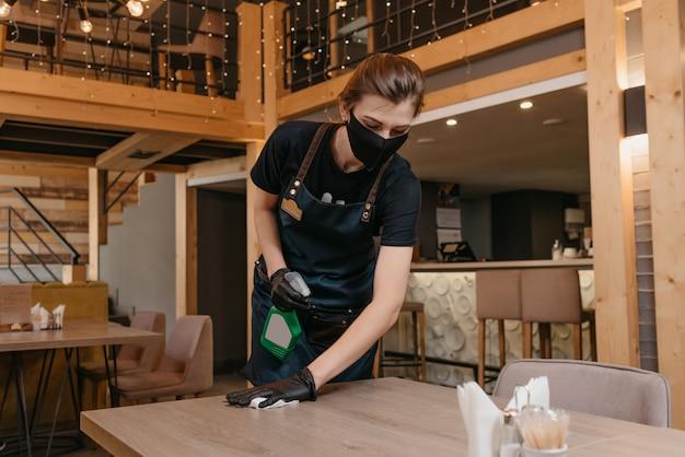 Официантка в черных одноразовых медицинских перчатках носит медицинскую маску
