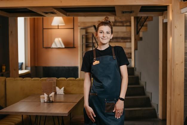 Молодая усмехаясь официантка представляя в ресторане