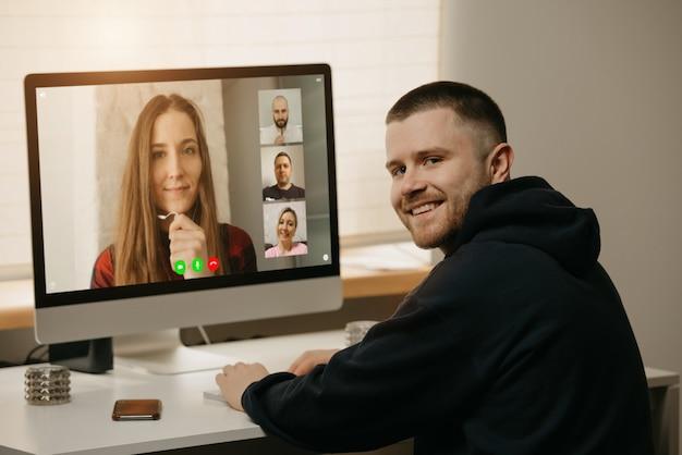 リモート作業。デスクトップコンピューターで同僚とビデオ通話中の男性の背面図。仲間は気が散り、自宅でのオンラインブリーフィングから微笑んでいます。