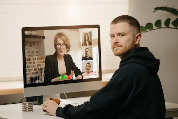 リモート作業。デスクトップコンピューターで同僚とビデオ通話中の男性の背面図。自宅でのオンラインブリーフィングから気を取られている仲間。