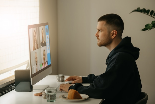 リモート作業。デスクトップコンピューターで同僚とビデオ通話中の男性。自宅からオンラインブリーフィングに熱心に取り組む仲間。