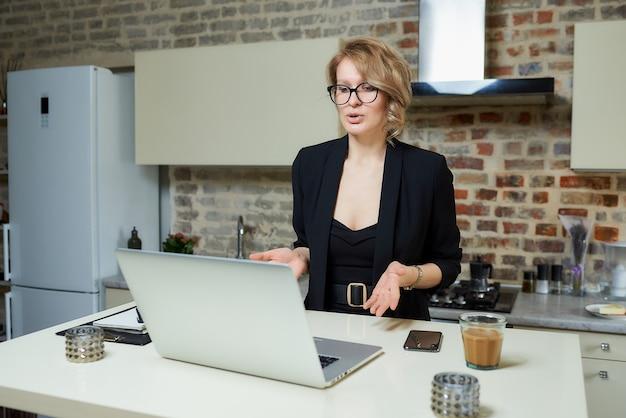 Женщина в очках работает удаленно на ноутбуке в своей кухне. блондинка, жестикулируя, обсуждает со своими коллегами онлайн-брифинг на дому.