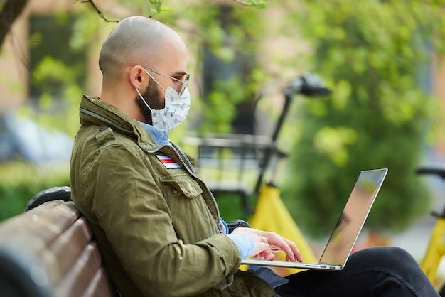 Человек в маске, чтобы избежать распространения коронавируса, работает удаленно на ноутбуке в парке. парень в темных очках сидит на скамейке на улице с компьютером возле велосипеда. бело-красно-белый флаг.