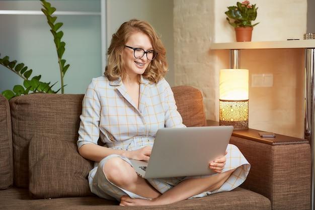 Женщина в платье сидит на диване со скрещенными ногами и работает на ноутбуке в своей квартире. девушка с брекетами смотрит вебинар.
